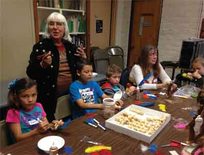 The Lost City Museum volunteer Stella Stutz-Robinson helps local youth make rattlesnakes, Kachina Dolls and Pueblo crafts during the annual  Kid's Day on Saturday at the museum. PHOTO BY STEPHANIE BUNKER/Moapa Valley Progress.