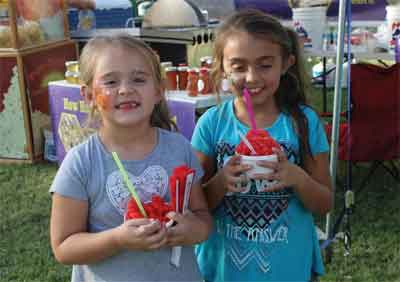 Lyla and Nadia Shakespear enjoy shave ice during the Logandale Fall Festival last weekend. PHOTO BY VERNON ROBISON/Moapa Valley Progress.