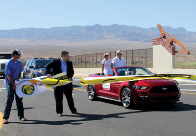 Mesquite Mayor Al Litman and his wife break through the ceremonial ribbon as they ride in the first car across the new overpass. Holding one end of the ribbon is Jed Wheeler (far left), of Meadow Valley Construction, and Kent Alexander, representing Rep. Cresent Hardy. PHOTO BY VERNON ROBISON/Moapa Valley Progress.
